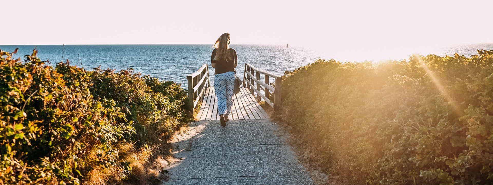 Frau läuft Richtung Meer zu einem Steg am Wasser - Sonne, Sommer, Meer